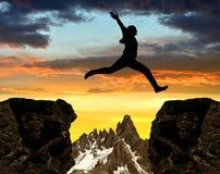 Девушка скача над зазором стоковое фото rf