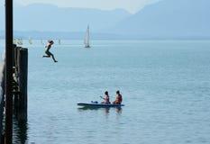 Девушка скача от высокой пристани для того чтобы намочить и 2 других на каяке Стоковая Фотография RF