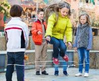 Девушка скача пока игра веревочки скачки с друзьями Стоковое Изображение RF