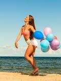 Девушка скача с красочными воздушными шарами на пляже Стоковая Фотография RF