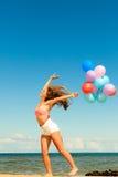 Девушка скача с красочными воздушными шарами на пляже Стоковые Фотографии RF