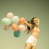 Девушка скача с красочными воздушными шарами на пляже Стоковое Изображение RF