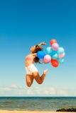 Девушка скача с красочными воздушными шарами на пляже Стоковые Изображения