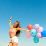 Девушка скача с красочными воздушными шарами на пляже Стоковое Изображение