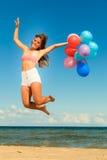 Девушка скача с красочными воздушными шарами на пляже Стоковое фото RF