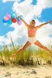 Девушка скача с красочными воздушными шарами на пляже Стоковая Фотография