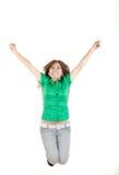 Девушка скача с поднятыми оружиями вверх утехи возбудила изолированный на whi стоковое фото