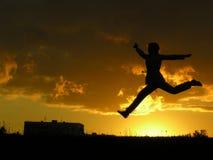 девушка скачет заход солнца стоковое фото rf
