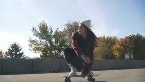 Девушка скейтбордиста в белой шляпе и рубашке шотландки едет скейтборд outdoors Девушка хипстера skateboarding в парке сток-видео