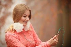 Девушка слушая к музыке в парке осени Стоковое фото RF