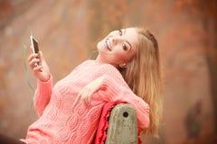Девушка слушая к музыке в парке осени Стоковые Фото