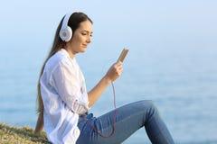 Девушка слушая к онлайн музыке на пляже Стоковая Фотография RF