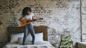Девушка смешанной гонки молодая смешная играя акустическую гитару и имеет танцы потехи на кровати дома видеоматериал