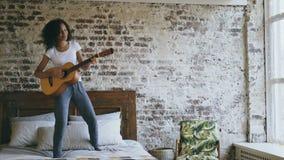 Девушка смешанной гонки молодая смешная поя и играя акустическую гитару пока имейте танцы потехи на кровати дома видеоматериал
