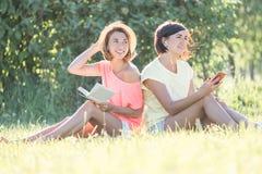 Девушка 2 смеясь над на траве Стоковое Изображение RF