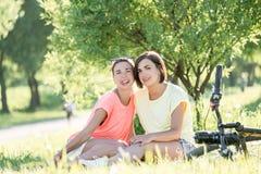 Девушка 2 смеясь над на траве Стоковые Изображения RF