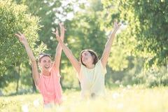 Девушка 2 смеясь над на траве Стоковое Изображение