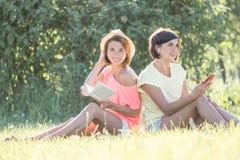 Девушка 2 смеясь над на траве Стоковое фото RF