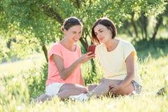 Девушка 2 смеясь над на траве Стоковое Фото
