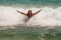 Девушка смеясь над и плача в брызге волн на Стоковое Изображение RF