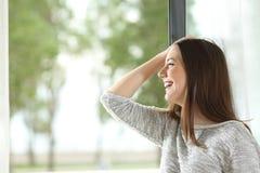 Девушка смеясь над и смотря через окно Стоковая Фотография RF