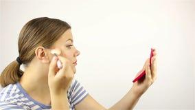 Девушка смотрит в зеркале и пудрит ее сторону сток-видео