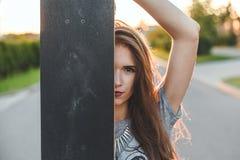 Девушка смотрит из доски конька брюнет стильного внешнего портрета красивое Стоковое Изображение RF