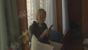 Девушка смотрит и трясет телефон видеоматериал
