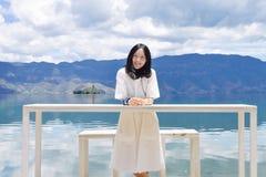 Девушка смотрит камеру стоя за высокой таблицей Стоковые Фото