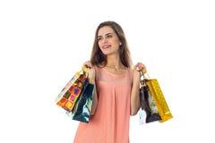 Девушка смотрит к стороне и держит 2 руки различных покрашенных сумок изолированных на белой предпосылке Стоковые Изображения RF