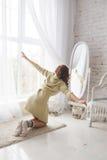Девушка смотрит себя в зеркале Стоковое Фото