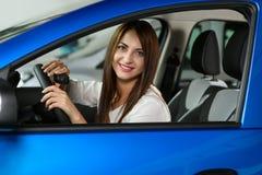 Девушка смотрит счастливой в новом автомобиле стоковое изображение rf