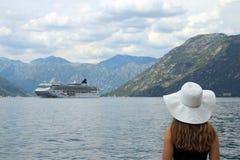 Девушка смотрит туристическое судно входя в лето залива Kotor стоковая фотография rf