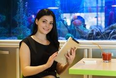 Девушка смотрит фото используя серебряную цифровую таблетку стоковые фотографии rf