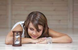Девушка смотрящ hourglas стоковые изображения rf