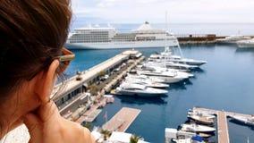 Девушка смотря вкладыш круиза от террасы гостиницы, ждать embarkation на корабле стоковое изображение