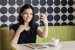 Девушка смотря в зеркале тщеты сидя на таблице стоковое изображение rf