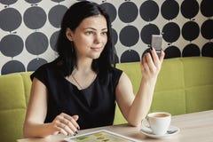 Девушка смотря в зеркале тщеты сидя на таблице стоковые фото