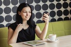 Девушка смотря в зеркале тщеты сидя на таблице стоковое фото