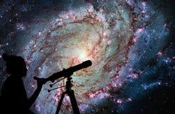 Девушка смотря звезды с телескопом Более Messier 83 стоковое фото