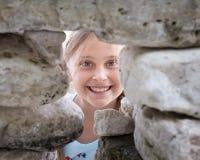 Девушка смотря камеру через отверстие в стене утеса Стоковые Изображения RF