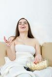 Девушка смотря кино или ТВ смеясь над имеющ потеху есть попкорн стоковое изображение rf