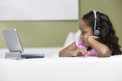 Девушка смотря кино на портативное DVD-плеер Стоковые Фото