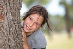 Девушка смотря от за дерева Стоковые Изображения