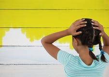 Девушка смотря покрашенную желтую стену Стоковые Изображения RF