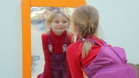 Девушка смотря себя в передергивая зеркале видеоматериал