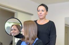 Девушка смотря себя на зеркале парикмахера Стоковые Изображения RF
