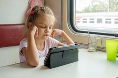 Девушка смотря таблетку в поезде Стоковая Фотография RF