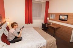 Девушка смотря ТВ в кровати Стоковое Изображение