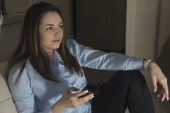 Девушка смотря ТВ в темноте с телефоном стоковое изображение